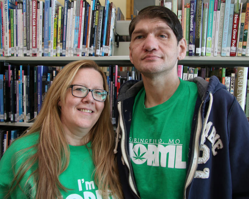 Kimberly Ruiz, left, stands over a head lower than her partner, Lonnie Kessler, right. She wears dark, black-rimmed glasses, they both wear bright green NORML shirts and smile into the camera.