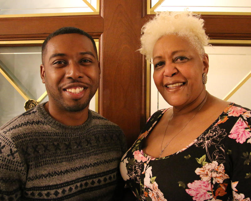 Devin Hursey, left, wears a patterned gray sweater, has a light beard and smiles into the camera. Jannis Evans, right, wears a floral-patterned top, large silver earrings and has short, white hair. She also smiles into the camera.