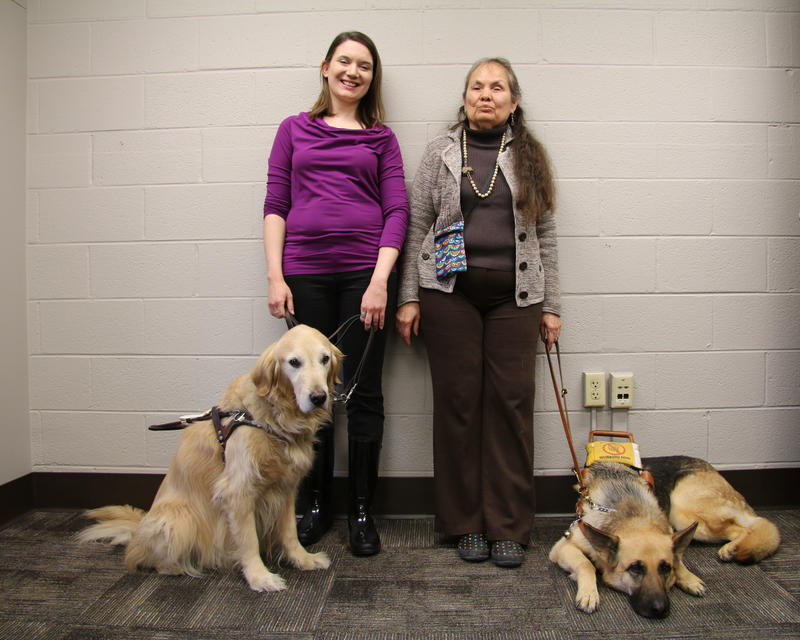 Grethen Maune, left, wears a bright purple shirt and her service dog, Keeper, a Golden Retriever, sits at her feet. DeAnna Quietwater Noriega, right, wears a brown knit cardigan and her service dog, Enzo, a German Shepard, lies at her feet. They all smile