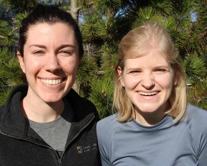 Samantha Dyroff, left, wears a gray sweatshirt and has dark brown hair. Megan Anderson, right, wears a gray, long-sleeved athletic shirt and has light blonde hair. They smile into the camera.