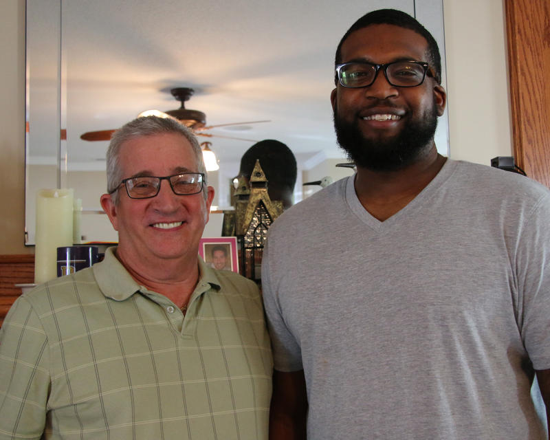 Glen Moritz, left, wears a green-striped polo and black rimmed rectangular glasses. Tamarr Maclin, rights, wears a gray t-shirt, has a close-shaved black beard and wears black rimmed glasses. They smile into the camera.