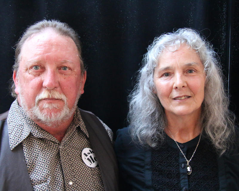 John and Donna LaBelle stand side-by-side. John, left, is wearing a patterned shirt and a leather vest.  Donna, right, has long light-colored hair and wears a black shirt.