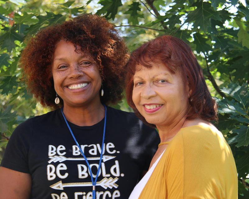Verna Laboy, left, wears a dark blue t-shirt and smiles into the camera. Annabelle Simmons, right, wears a bright yellow shirt and smiles into the camera.