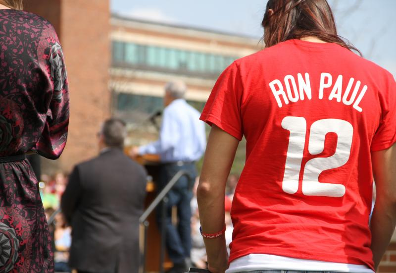 A supporter wearing a Ron Paul t-shirt looks on as Presidential candidate Ron Paul makes a speech on the south end of the David R. Francis Quadrangle on the University of Missouri campus on Thursday, March 15, 2012.
