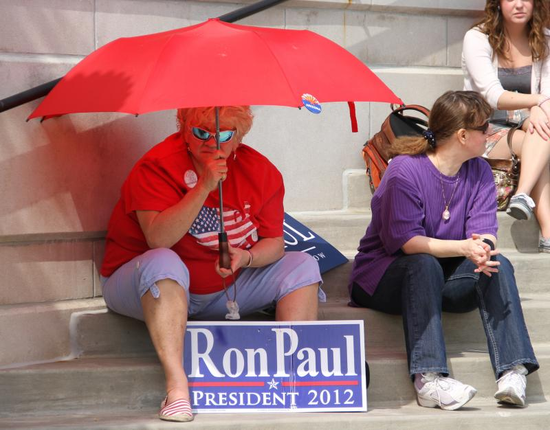 A supporter of Presidential candidate Ron Paul shades herself with an umbrella as he makes a speech on the south end of the David R. Francis Quadrangle on the University of Missouri campus on Thursday, March 15, 2012.