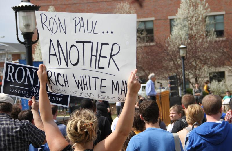 A woman holds an anti-Ron Paul sign as he makes a speech on the south end of the David R. Francis Quadrangle on the University of Missouri campus on Thursday, March 15, 2012.
