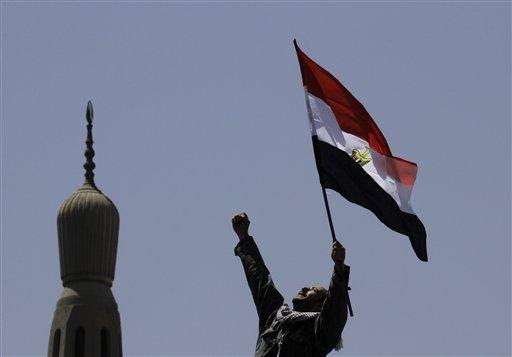An Egyptian protester chants slogans and waves a national flag in front of a minaret at Cairo's Tahrir Square. The country experienced a flourishing of new media outlets after the ouster of President Hosni Mubarak.