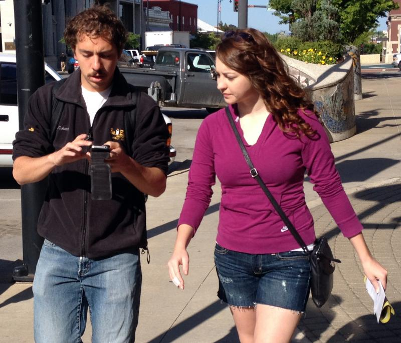 "MU senior Max Smith, left, uses his smartphone to navigate around Columbia with senior Amanda Vanslyke. The students are particpating in the university's ""REBOOT Mizzou"" project, which teaches sustainable practices through a game format."