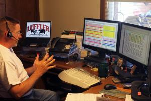 Rural commodities broker Tom Leffler checks the markets and speaks to a client on the phone.