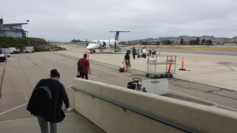 Passengers leaving the current terminal as they board a plane on the tarmac.