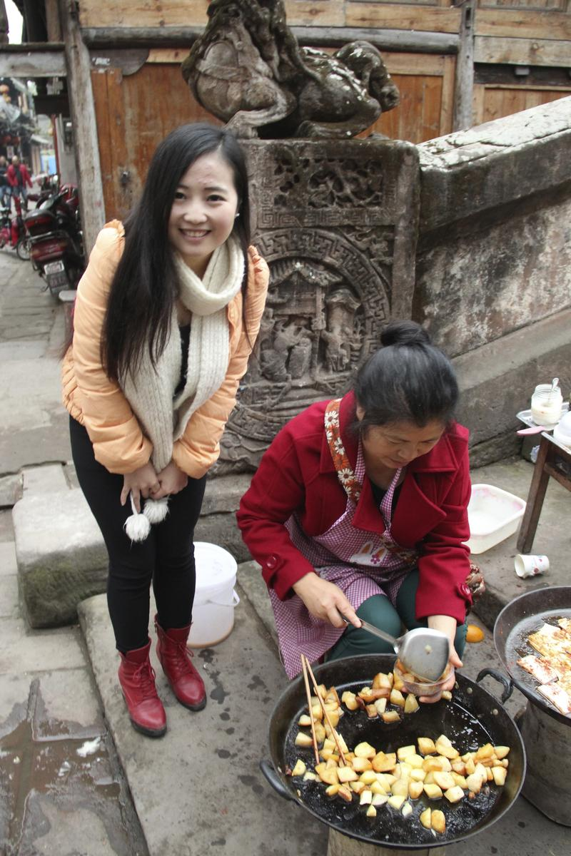 Tiffiny Shi Shi visits with street vendor at Leshan Bridge in Pingle Ancient Town