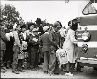 Japanese-American families board busses for internment camps during WWII