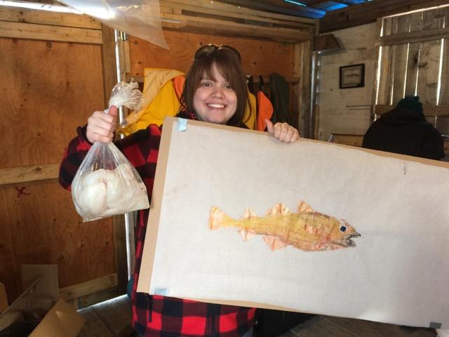 Arielle Przybysz, one of the girls in the Girls Who Fish Program. She is holding fresh fillets from the cod that she caught, and a gyotaku painting of her fish