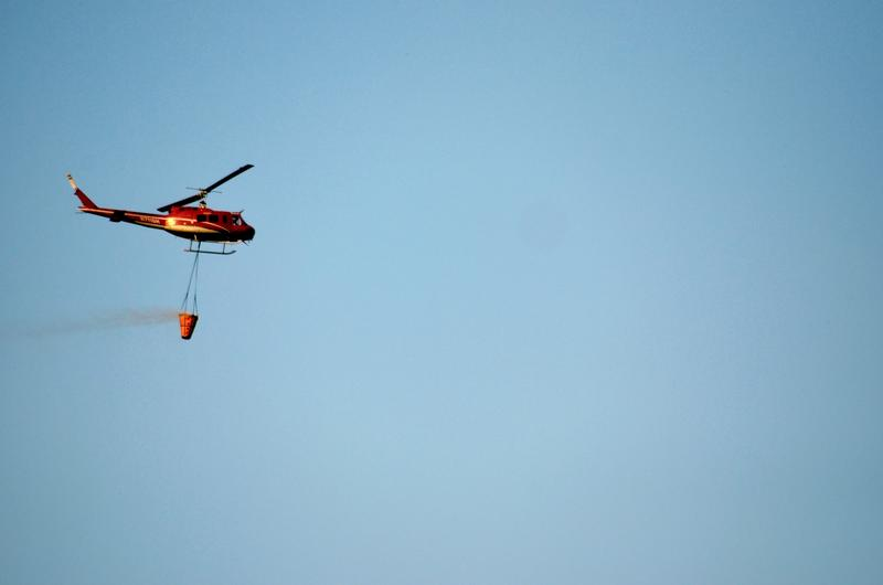 A helicopter dumps water from Lake Cachuma onto the Whittier Fire on Sunday.