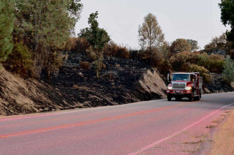 A fire truck drives along Highway 58 on Monday over roads coated with fire retardant.