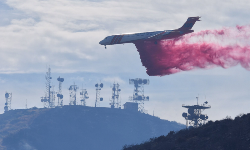 An Erickson MD-87 makes a phoschek drop near Santa Ynez Peak below West Camino Cielo.