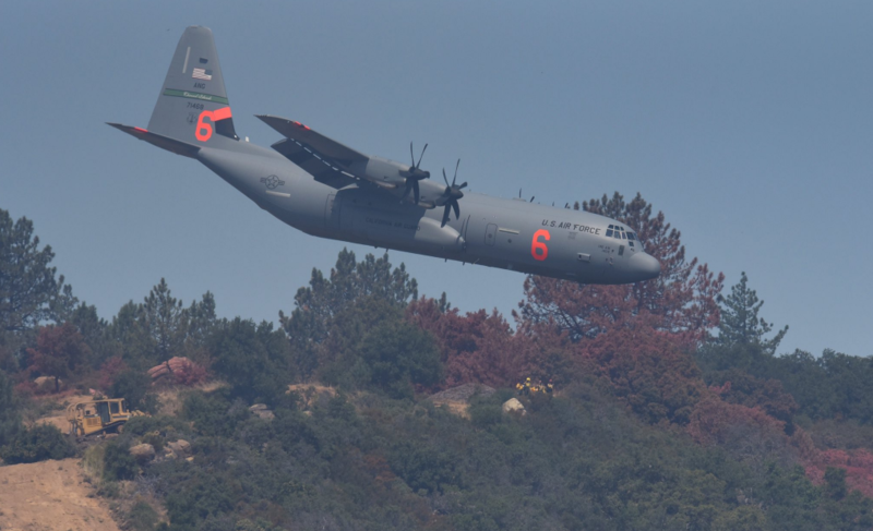 Along the western flank of the fire, a CA National Guard C-130 MAFF dips below West Camino Cielo to make a retardant drop.