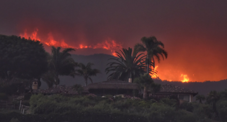 Flames burn in the distance behind a home near El Capitan Ranch