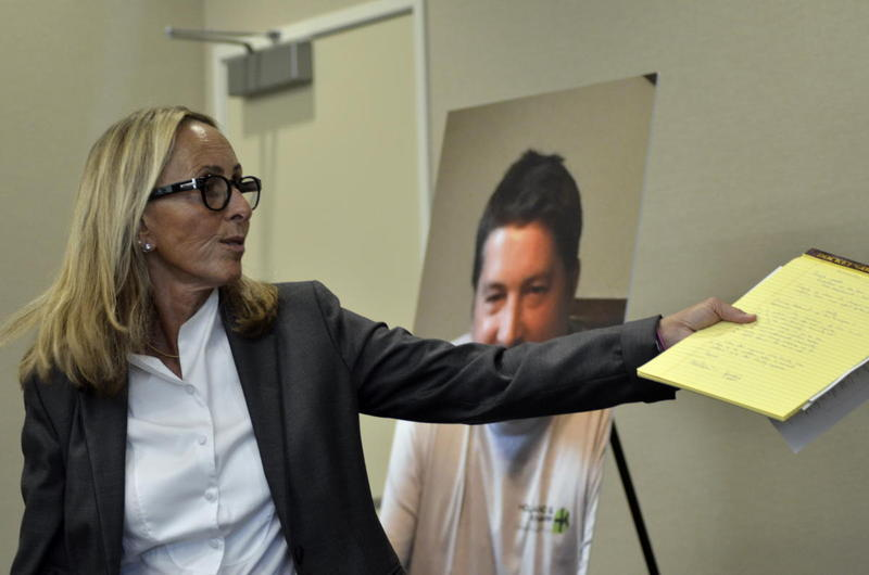 At a July press conference, Paula Canny - the Holland family's attorney - explains details of video footage she allegedly saw of the hours prior to Holland's death. Behind Canny is a family picture of Holland.