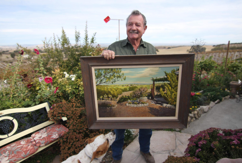 Richard Sauret stands near the garden and vineyard he planted in the 1960s, holding a painting of the same scene.