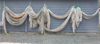 A cod trap hanging outside Leo's shed in Petty Harbour. Once important tools of the trade, Cod traps are now mostly decorative, having been replaced by more industrialized ways of fishing.