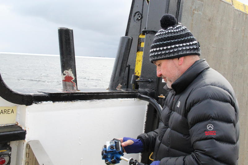 Videographer Jason Lopez sets up his 360 camera aboard a Washington Island Ferry