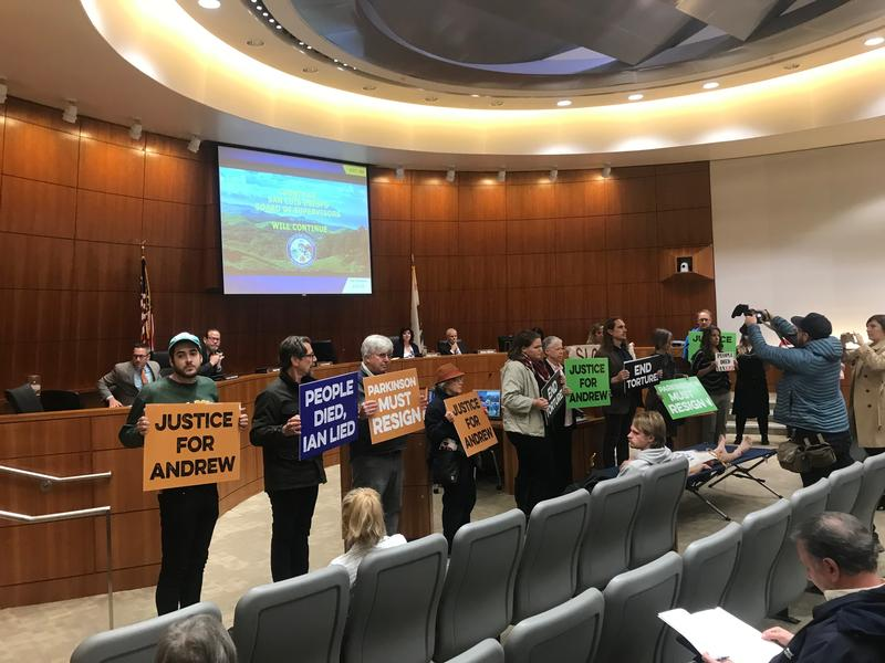 Demonstrators stand silently at the San Luis Obispo County Board of Supervisors meeting on March 21, 2018.
