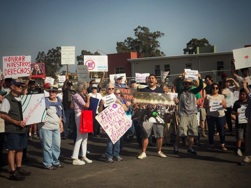 Protesters hold a rally outside an ICE facility in Santa Maria. One holds a photo from 2014 showing residents at a city council opposing the opening of the facility.