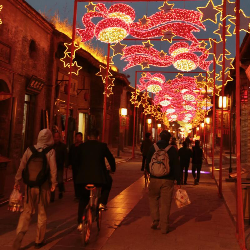 Hancheng Ancient Town street scene is lively with locals in the evening.