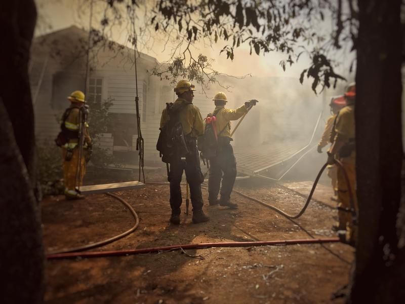 Firefighters work to take down an awning from a house that continued to burn and smolder into the morning hours during Goleta's July Holiday Fire.