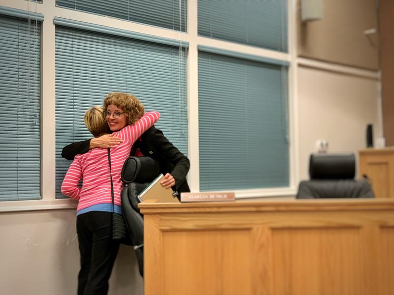 Outgoing Coast Unified School District superintendent Victoria Schumacher hugs a colleague after announcing she is retiring.