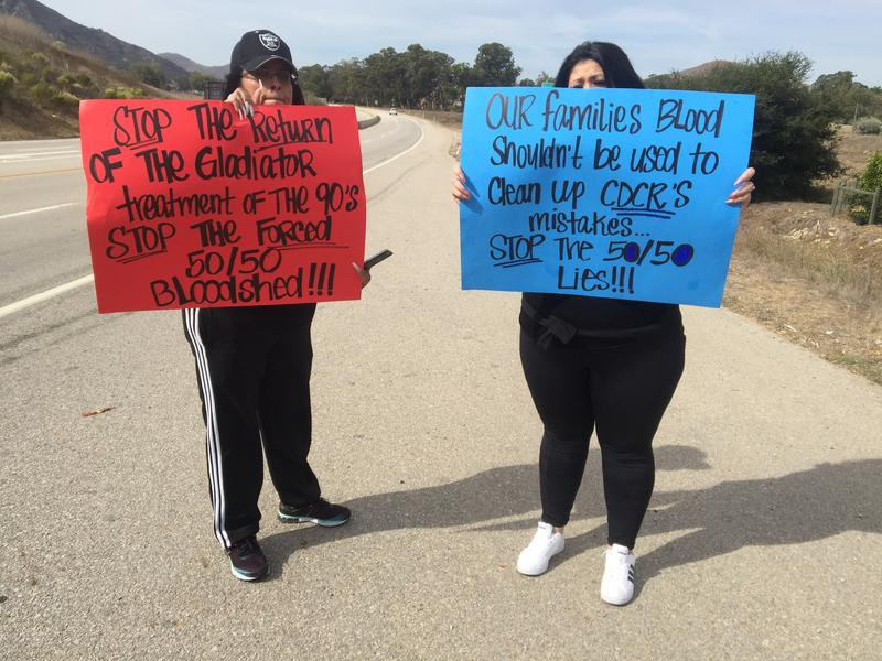 The wives of CMC inmates held signs Thursday along Highway 1 to raise awareness of the new policy.