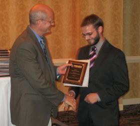 PRNDI Treasurer Bob Beck presents an award for multimedia presentation to KCCU reporter Mitch Watson at the organization's awards banquet in Cleveland, Ohio on June 22, 2013.