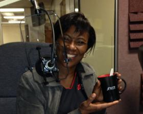 Station Manager and hand-model Cynthia Sosa displaying the new KCCU coffee mug.