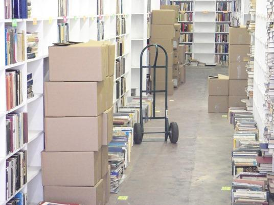 "Books being packed for removal after ""The Last Book Sale."""