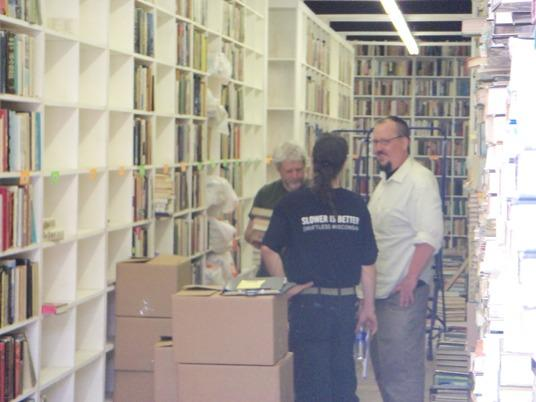 Paul Schaap (left) and Jon Guetschow (right) of Powell's Books chat with another dealer as they pack up their purchases.