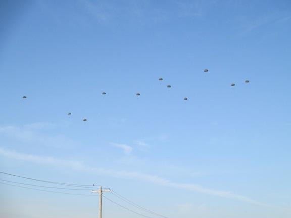 Parachutes dot the sky as the team makes its jump.