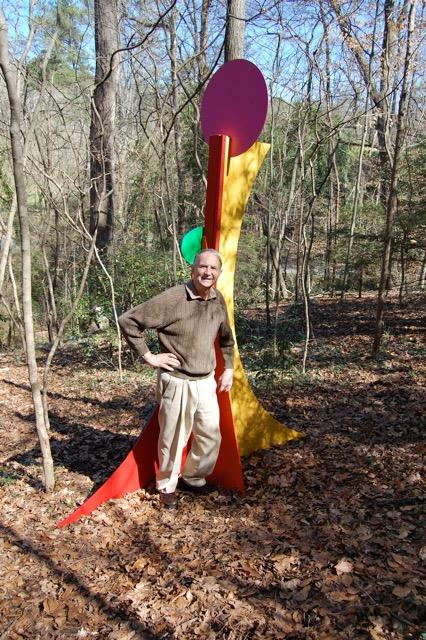 George de Man in his Atlanta home garden posing with one of his own color-work sculptures.