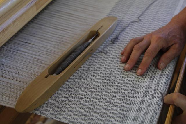 Sandy Fisher's hands resting on her current weaving project - a series of linen towels.