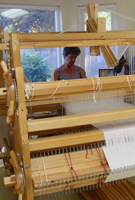 Sandy Fisher in her studio at her loom which is set up for weaving her linen towel series. Setting the base warp and weft lines - which include hundreds of individual threads, can take a full day of work or more.