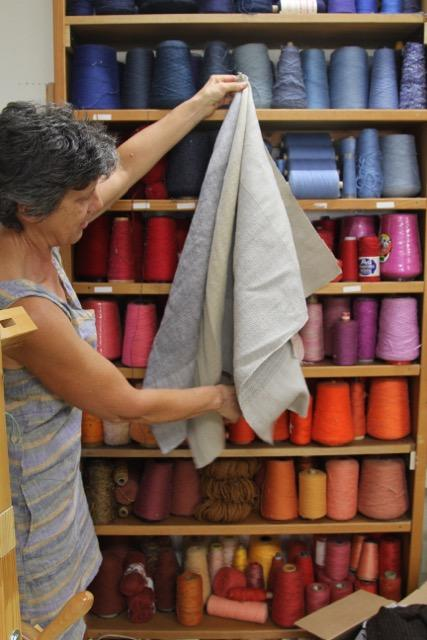 Sandy Fisher in her studio holding up three of the linen hand towel patterns in her series of five patterns.