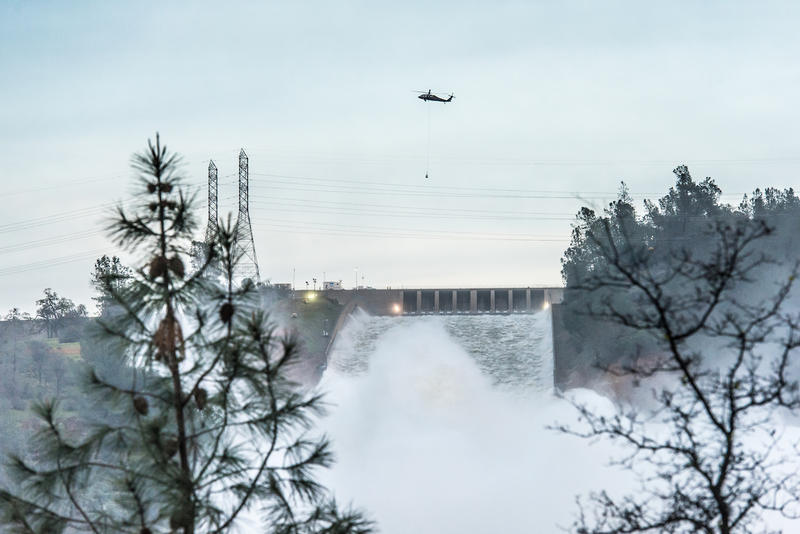 Helicopters transport large bags of rocks to the erosion site at the Oroville Dam auxiliary spillway to help fight further erosion.