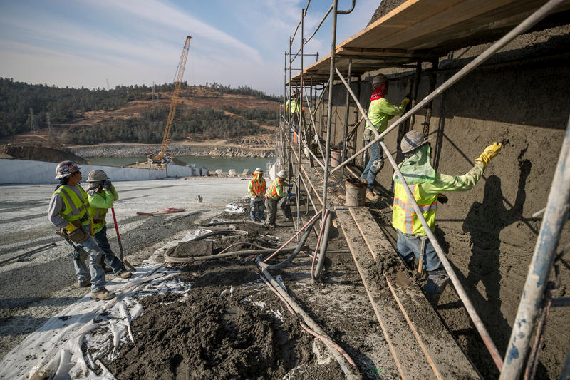 Workers from Superior Gunite shotcrete roller-compacted concrete on the sidewall between the upper and lower chutes of the Lake Oroville flood control spillway in Butte County, California. Photo taken October 17, 2017.