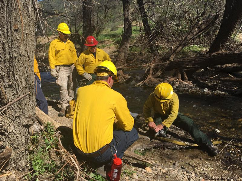 Veterans learn how to pump water out of a creek through a fire hose at Paramount Ranch