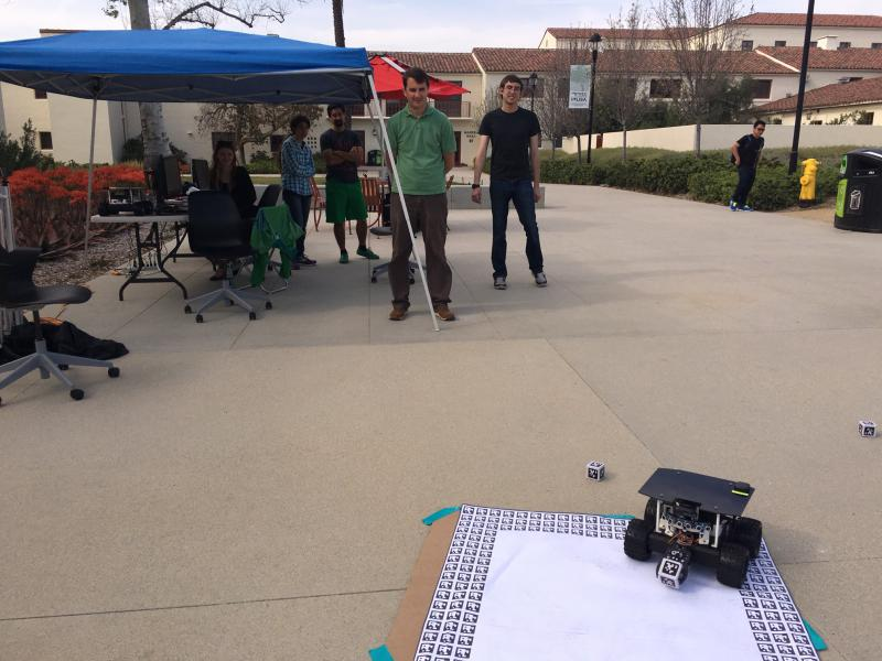 Jason Isaacs, assistant professor of computer science, and his students are testing their algorithm with one robot.