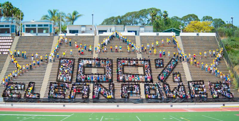 """Protesters in Santa Barbara line up to create a sun with the words """"100% Clean Energy."""""""