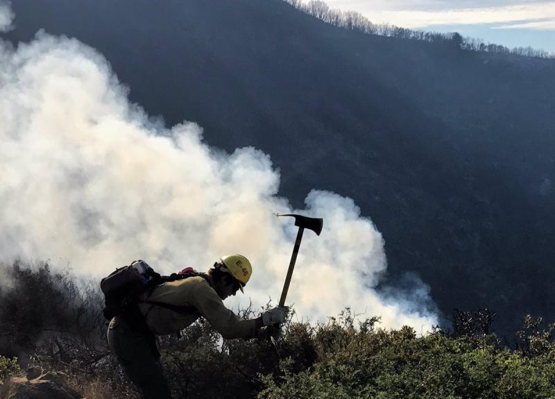 A firefighter on West Camino Cielo battling the Whittier brush fire