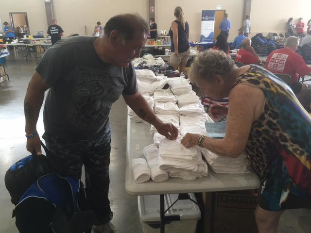 A homeless veteran picks ups clothing at a Stand Down event in Ventura, which offered food, clothing, and services to those in need
