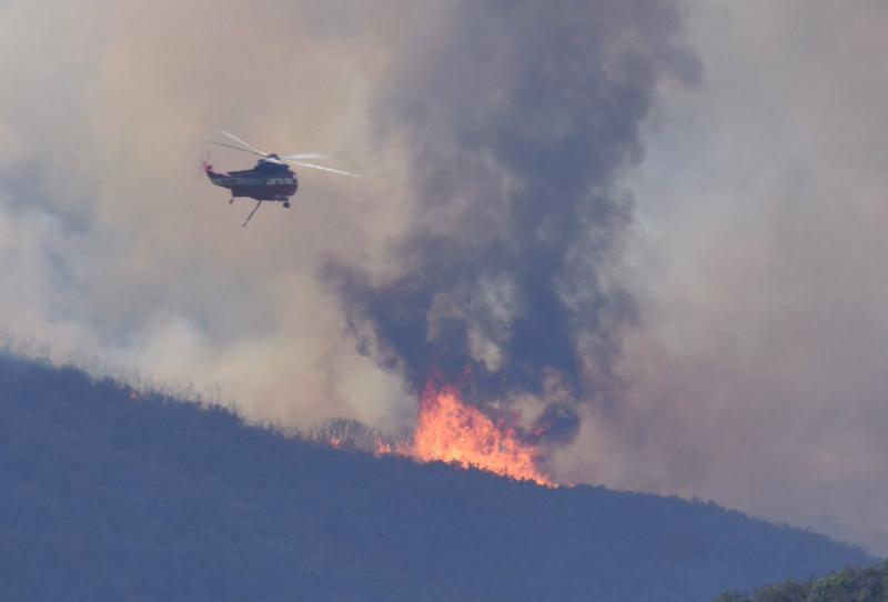 A helicopter prepares to make a water drop on Santa Barbara County's Whittier brush fire