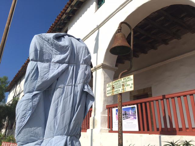 Damaged statue at Santa Barbara Mission covered with tarp